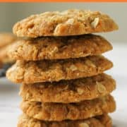 chewy anzac biscuits stacked on top of each other on a marble board.