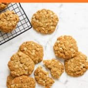 chewy anzac biscuits scattered on a marble background.