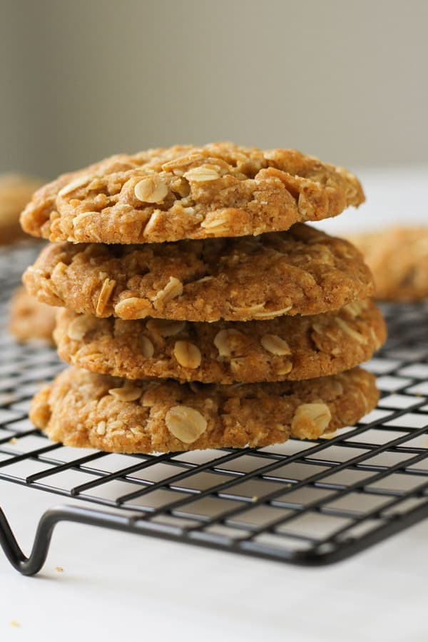 anzac biscuits stacked on top of each other on a wire rack.