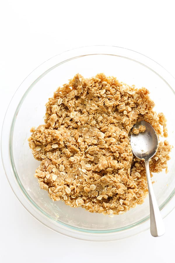anzac biscuit mixture in a glass mixing bowl.