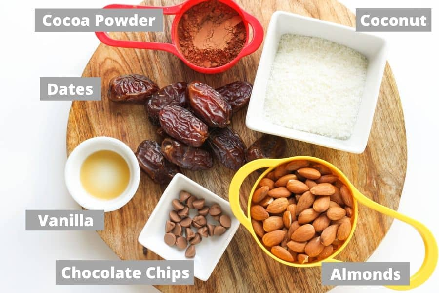 ingredients to make chocolate coconut energy balls on a wooden board.