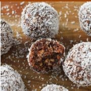 chocolate coconut energy balls on a wooden serving board.