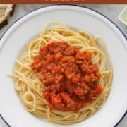 """image of finished dish with text overlay """"lentil bolognese - vegan""""."""