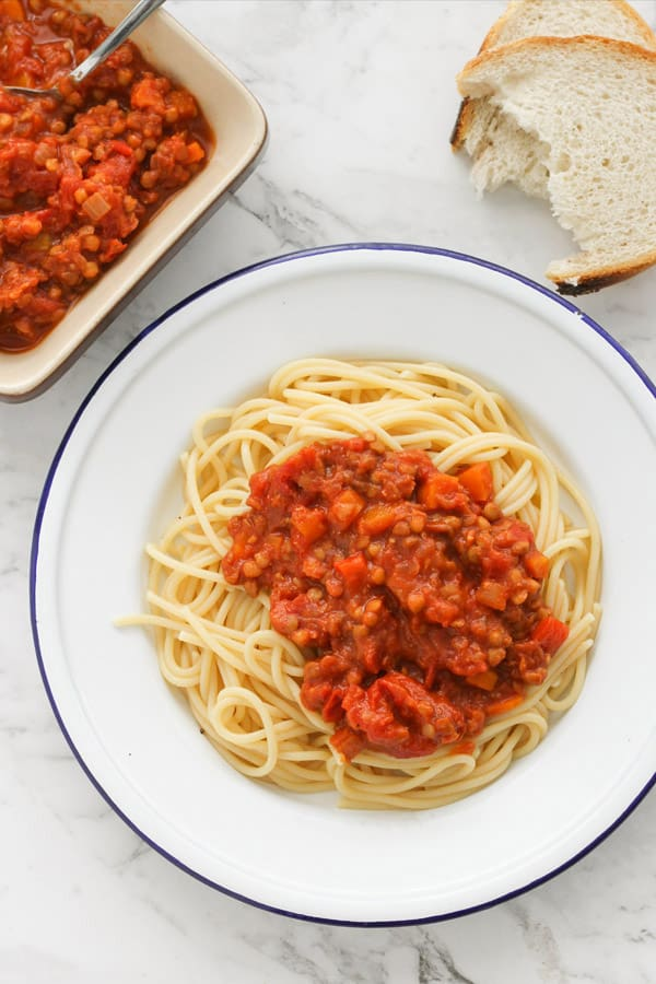 lentil bolognese on top of spaghetti on a white plate.