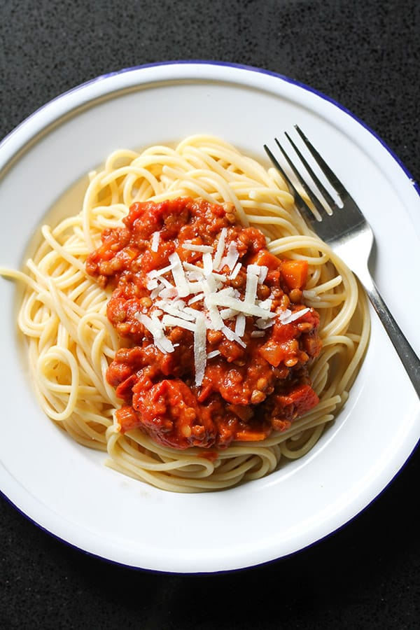 lentil bolognese on top of spaghetti with shaved parmesan.