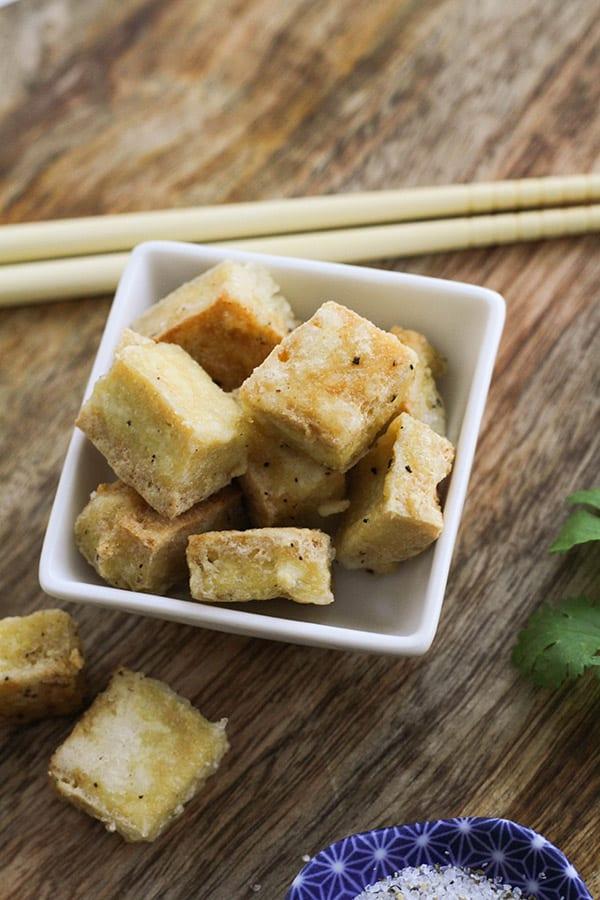 salt and pepper tofu bites in a square bowl.