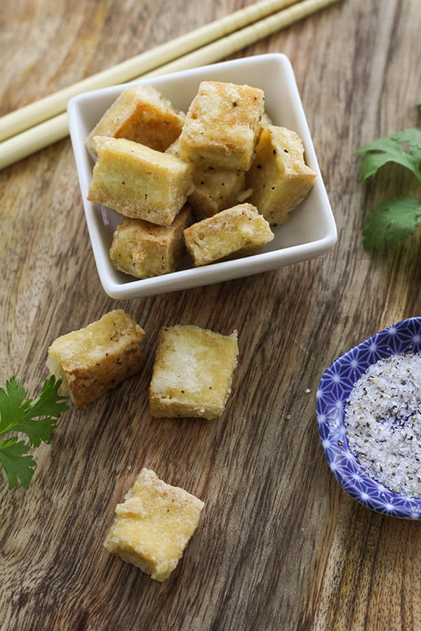 pieces of salt and pepper tofu scattered on a wooden board.