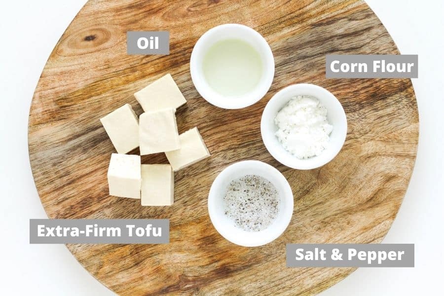 ingredients for salt and pepper tofu on a wooden board.
