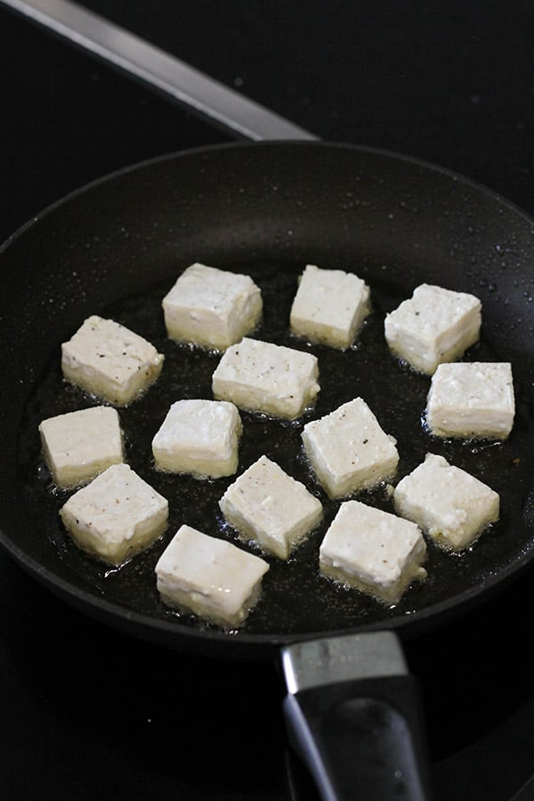 cubes of tofu being fried in a frying pan.