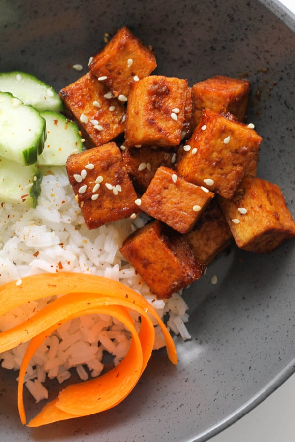 cubes of sriracha tofu on top of a bed of rice.