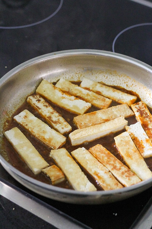 cooked tofu slices in a frying pan.