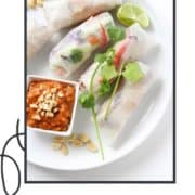 "rice paper rolls on a white plate with text overlay ""veggie rice paper rolls""."