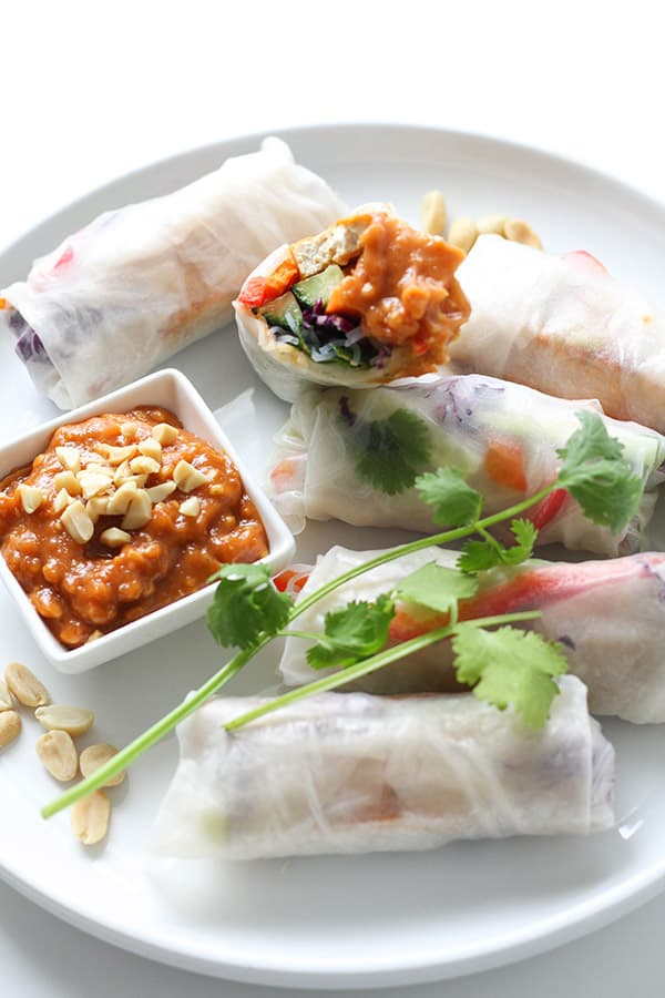 a white plate filled with rice paper rolls.