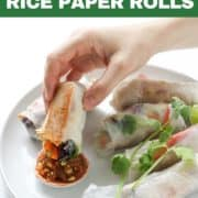 a hand dipping a rice paper roll into a peanut sauce.
