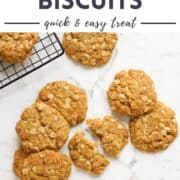 """cookies on a white marble counter top with text overlay """"chewy anzac biscuits""""."""