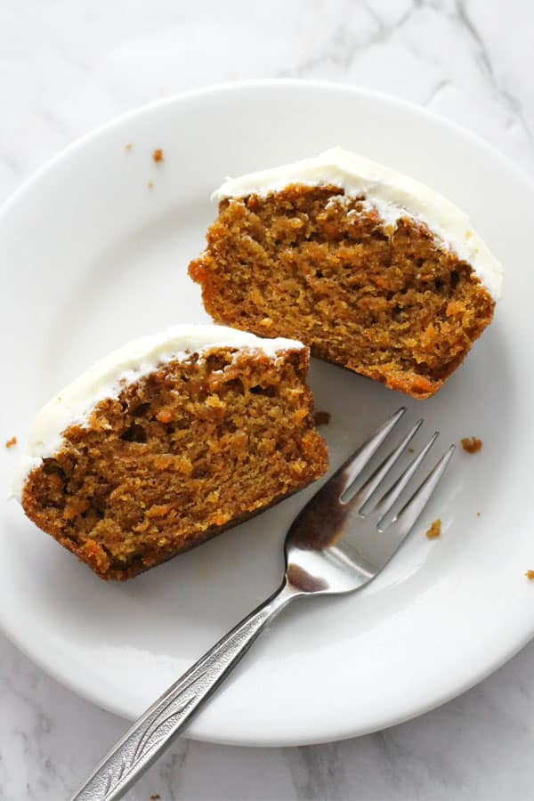 a cupcake cut in half on a white plate.