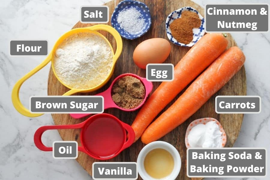 ingredients for carrot cupcakes on a wooden board.