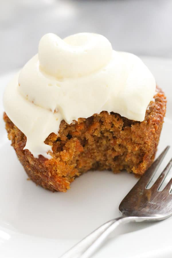 carrot cupcake on a white plate with a bite removed.
