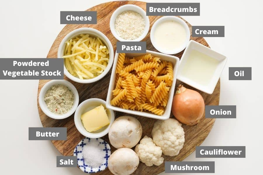 ingredients for creamy vegetable pasta on a wooden board.