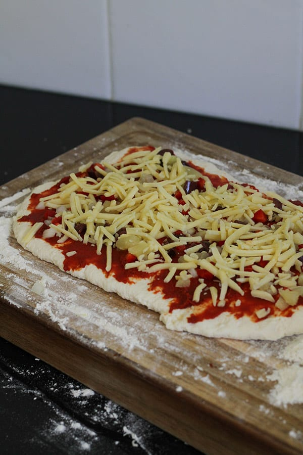 dough covered with toppings on a wooden board.