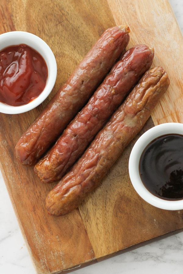 sausages on a wooden serving board.
