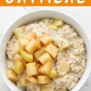 apple cinnamon oatmeal in a white bowl topped with stewed apples.