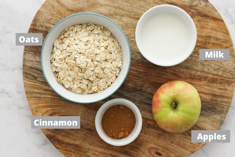 ingredients for apple cinnamon oatmeal on a wooden board.