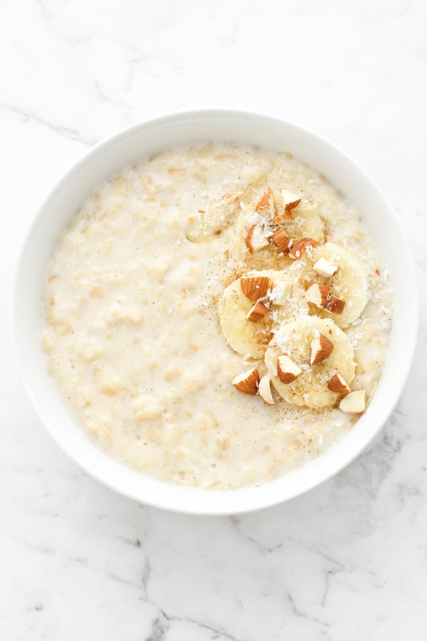 porridge in a white bowl topped with banana slices, cinnamon, almonds and coconut.
