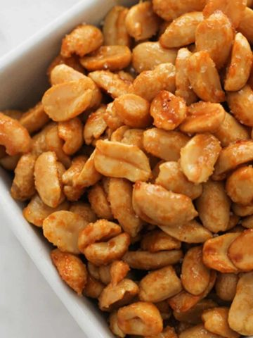honey roasted peanuts in a white bowl.