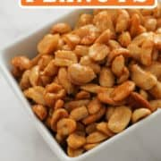 "white bowl of peanuts with text overlay ""honey roasted peanuts""."