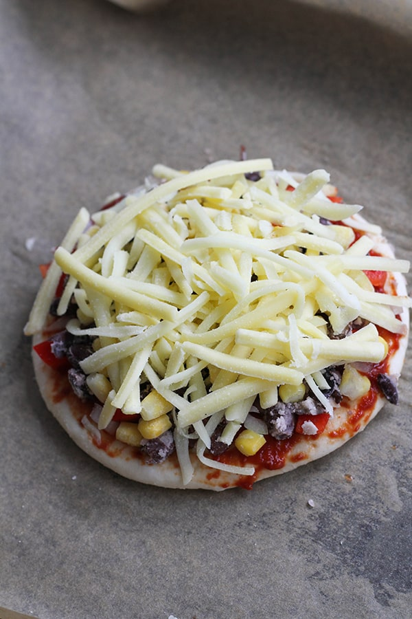 pizza base covered in cheese on a baking tray.