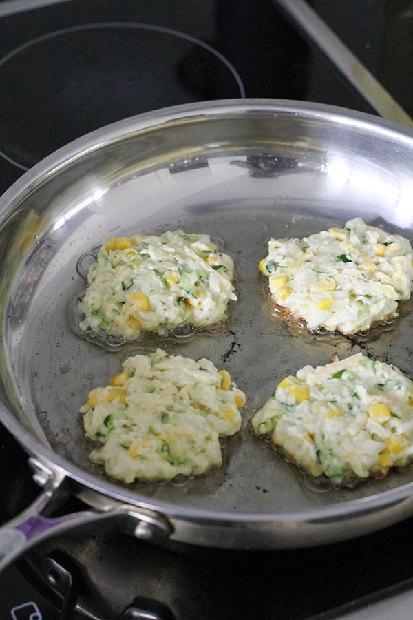 fritters cooking in a frying pan.
