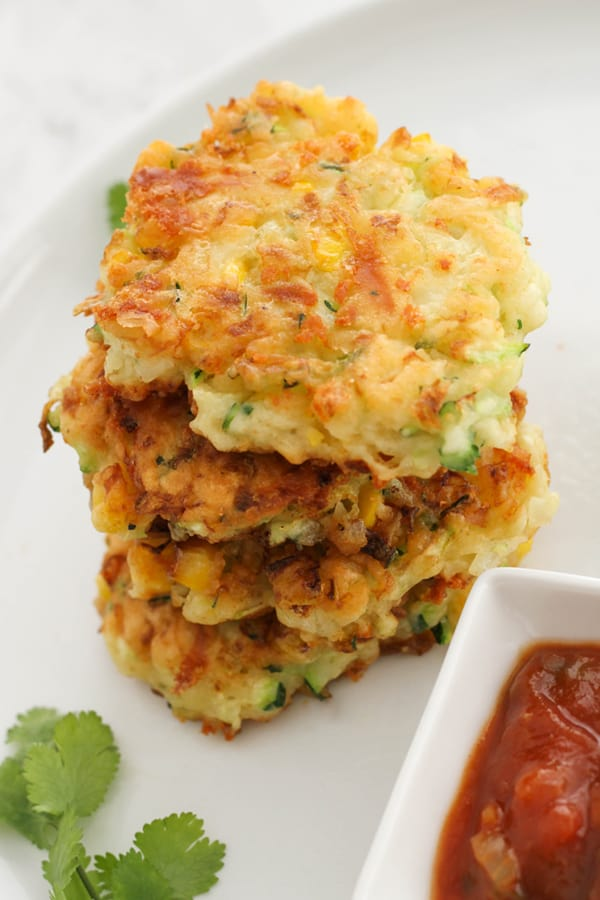 fritters stacked on top of each other on a white plate.