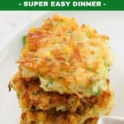 zucchini and corn fritters stacked on top of each other.