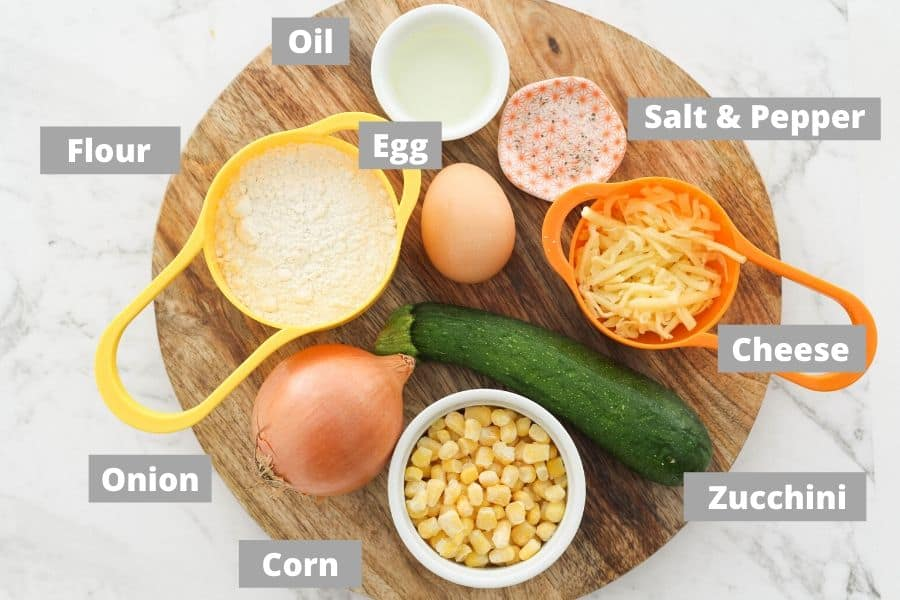 ingredients for fritters on a wooden platter.