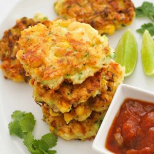 fritters stacked on top of each other on a white plate with salsa and limes.