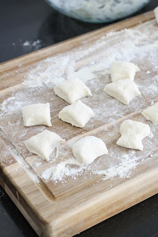 dough cut into bite-sized pieces on a wooden cutting board.
