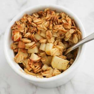 apple crisp in a white ramekin with a spoon.