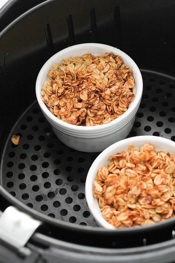two ramekins filled with apple crisp in an air fryer basket.
