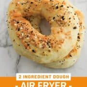 "bagels on a grey plate with text overlay ""2 ingredient dough - air fryer bagels""."