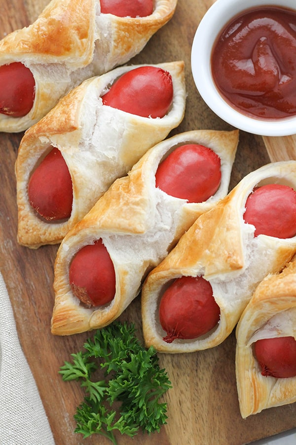 pigs in a blanket on a wooden serving board.