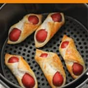 "pigs in a blanket in an air fryer basket with text overlay ""air fryer pigs in a blanket""."