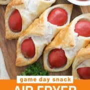 """pigs in a blanket on a wooden serving board with text overlay """"air fryer pigs in a blanket""""."""