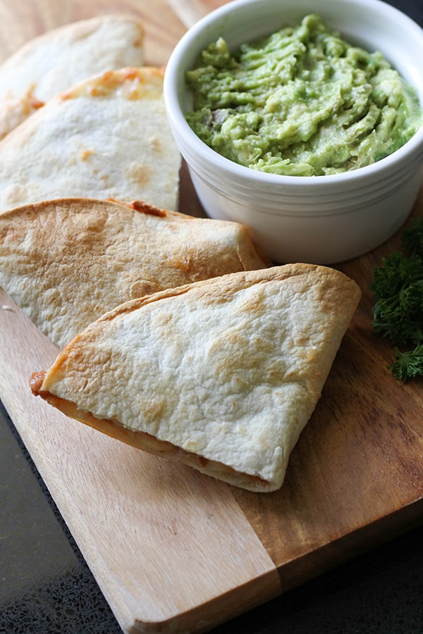quesadilla quarters on a wooden board with a bowl of guacamole.