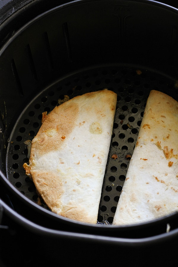 quesadillas in an air fryer basket.