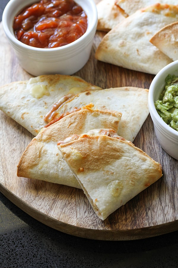quesadilla quarters on a wooden board with guacamole and salsa.