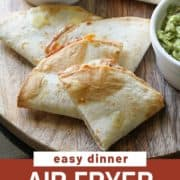 """quesadilla quarters on a wooden board with text overlay """"air fryer quesadillas""""."""