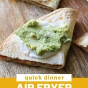 "quesadilla quarters topped with avocado and greek yoghurt on top on a wooden board with text overlay ""air fryer quesadillas""."
