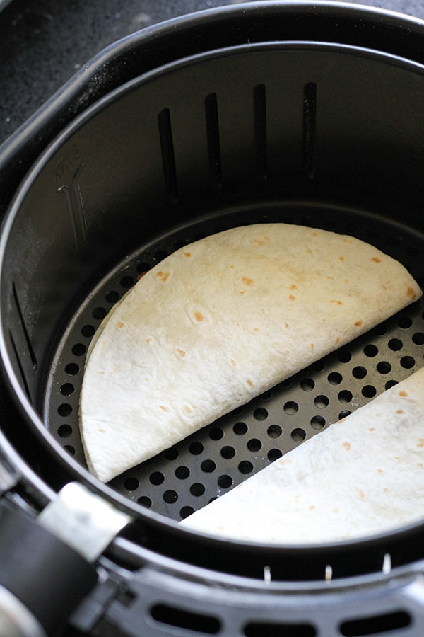quesadillas in an air fryer basket ready to be cooked.
