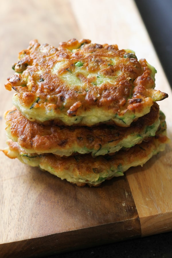 pea & feta fritters stacked on top of each other on a wooden board.